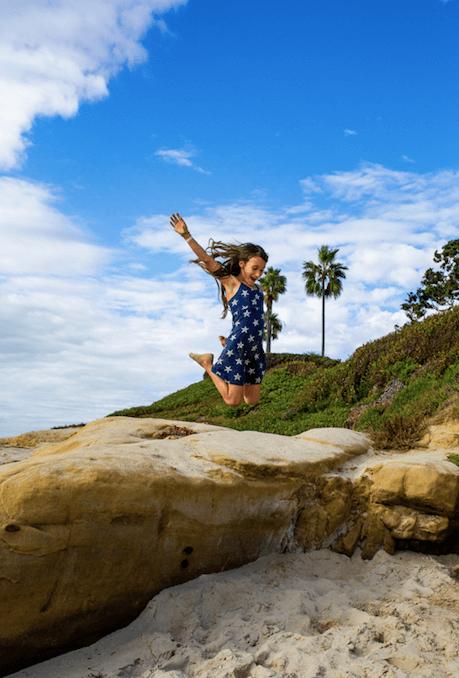 tati jumping at beach